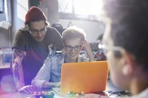 Designers travaillant ensemble sur ordinateur portable en atelier — Photo de stock