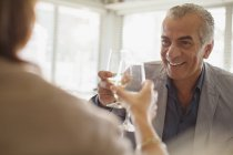 Smiling senior man drinking wine, toasting wine glasses with woman at restaurant — Stock Photo