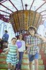Crianças correndo na frente do carrossel, mãe seguindo-os — Fotografia de Stock