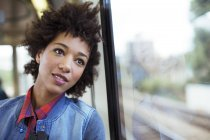 Daydreaming woman looking out train window — Stock Photo