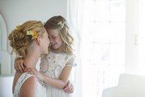 Невесты и подружки невесты, лицом друг к другу и улыбаясь в спальне — стоковое фото