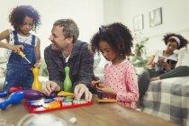 Multi-ethnischen Vater und Töchter spielen mit Spielzeug im Wohnzimmer — Stockfoto