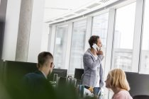 Businessman talking on cell phone at office window — Stock Photo