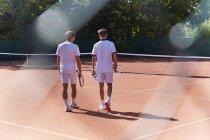 Молоді чоловіки тенісистів прогулянки з тенісних ракеток на Сонячний глини тенісний корт — стокове фото
