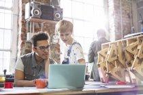 Des designers sérieux et concentrés travaillant sur un ordinateur portable dans un atelier — Photo de stock