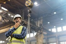 Steel worker with walkie-talkie in factory — Stock Photo