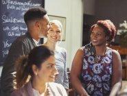 Sonrientes amigos hablando en el bar junto - foto de stock