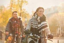 Smiling young couple bike riding on urban autumn street — Stock Photo