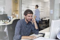 Businessman talking on cell phone working at computer in office — Stock Photo