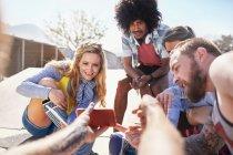 Homme de point de vue personnel montrant les amis vidéo sur téléphone intelligent à ensoleillé skate park — Photo de stock