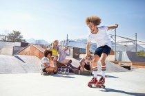Freunde, beobachtete Man Rollschuhlaufen im sonnigen Skatepark — Stockfoto