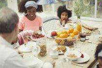 Familia joven multiétnica desayunando en la mesa - foto de stock