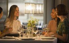 Улыбающиеся подруги обедают и пьют вино за столом ресторана — стоковое фото