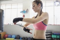 Young female boxer wrapping wrists in gym — Stockfoto