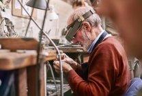 Gioielliere che indossa una lente d'ingrandimento per fascia che lavora in officina — Foto stock