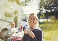 Porträt lächelnde Frau trinkt Kaffee vor sonnigem Wohnmobil — Stockfoto