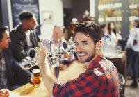 Retrato sorridente, confiante barman masculino servindo cerveja no bar — Fotografia de Stock