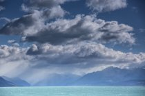 Nuages duveteux ci-dessus tranquille bleu lac Pukaki, Île du Sud, Nouvelle-Zélande — Photo de stock