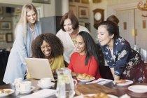 Sourire des amis femmes utilisant l'ordinateur portable à la table de restaurant — Photo de stock