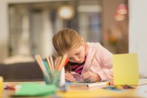 Целенаправленные девушка рисунок, делают поделки в таблице — стоковое фото