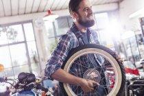 Усміхаючись мотоцикл механік балансова колесо в магазин — стокове фото
