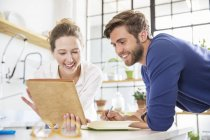 Two young people looking at documents in domestic kitchen — Stock Photo