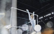 Female gymnast with arms raised below uneven bars in arena — Stock Photo