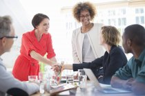 Office workers shaking hands at desk — Stock Photo