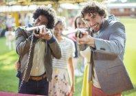 Молоді люди, прагнучи гармати в Луна-парк — стокове фото