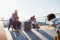 Friends pushing each other on skateboards at sunny skate park — Stock Photo