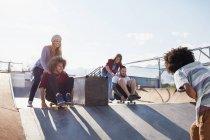 Amici che si spingono a vicenda sugli skateboard al Sunny Skate Park — Foto stock