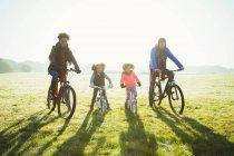 Портрет молодой семьи езда на велосипеде в солнечной траве осеннего парка — стоковое фото