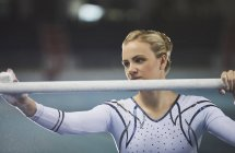 Female gymnast using chalk on uneven bars in arena — Stock Photo