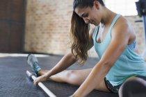 Konzentrierte sich die junge Frau Bein Strecken, mit Langhantel in Fitness-Studio — Stockfoto