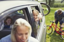 Portrait smiling girl with family inside car — Stock Photo