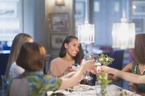 Smiling women friends toasting white wine glasses dining at restaurant table — Stockfoto
