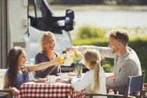 Семья пьет кофе и стаканы апельсинового сока за столом возле солнечного дома на колесах — стоковое фото