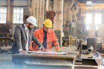 Manager e ingegnere lavoratore dell'industria siderurgica, rivedere le cianografie in fabbrica — Foto stock