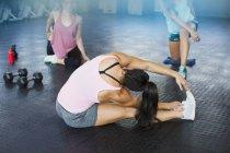 Junge Frau, die Dehnung Bein und Seite im Fitness-Studio — Stockfoto