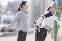 Female runners stretching on sunny sidewalk — Stockfoto
