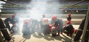 Equipage de stand remplaçant les pneus sur la formule 1 voiture de course dans pit lane — Photo de stock