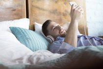 Людина, що слухати музику з навушниками і mp3-плеєр, лежачи на ліжку — стокове фото