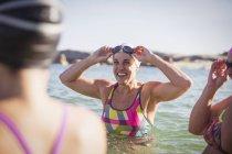 Улыбающиеся женщина активный пловцов на океан на открытом воздухе — стоковое фото