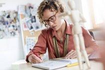 Зосереджено жіночий дизайн професійний замальовок у блокноті в офісі — стокове фото