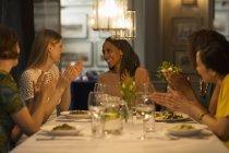 Sonriente mujer amigos cenando y celebrando aplaudiendo en mesa de restaurante - foto de stock