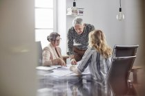 Architetti che esaminano le planimetrie delle riunioni in sala conferenze — Foto stock