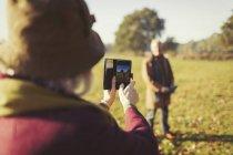 Ältere Frau mit Kamera Handy fotografierte Mann in sonnigen Herbst park — Stockfoto