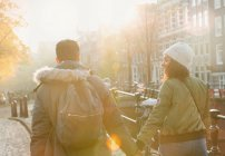 Young couple holding hands walking on sunny urban autumn street, Amsterdam — Stockfoto