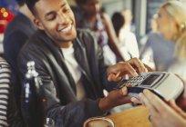 Smiling man paying bartender using credit card reader at bar — Stock Photo