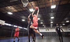 Young male basketball players playing basketball on court in gymnasium — Stock Photo